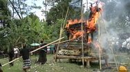 Stock Video Footage of Men use long poles to poke at a funeral pyre during a