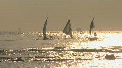 Sailboats coast across a shimmering sea. Stock Footage