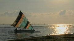 A colorful sailboat approaches a shoreline. Stock Footage