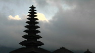 Stock Video Footage of A Balinese temple stands silhouetted against a cloudy sky.