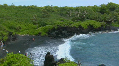A high angle shot over waves rolling into a black sand - stock footage
