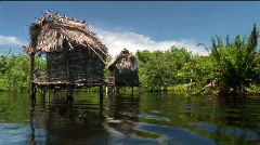 Thatched-roofed homes on stilts stand in a tropical river area. Stock Footage