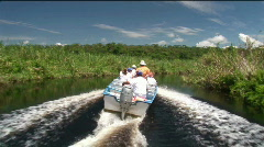 A tourist motorboat  travels through a wetland river area. Stock Footage