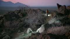 Cyclists travel rough trails in a desert area near dusk with head lights. Stock Footage