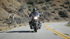 A man rides a motorcycle down a mountain road. Stock Footage