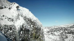 A skier jumps off the side of a mountain, and another person sits below. Stock Footage