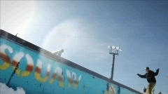 A snow-boarder slides on the edge of a long wall. Stock Footage