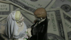 A married couple figurine stands amid twenty dollar bills. Stock Footage