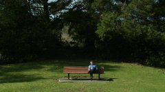 A man sits on a park bench alone with a flower. Stock Footage