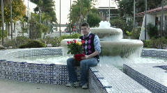 A man waits excitedly at a fountain with flowers Stock Footage