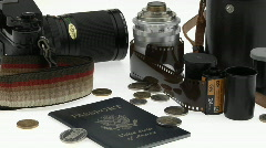A passport, coins, camera and equipment sit on a white table. Stock Footage