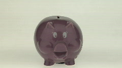A woman's hand puts a coin into a pink piggy bank. Stock Footage