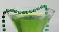 Beads of green dice adorn a cocktail glass. Stock Footage