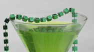 Stock Video Footage of Beads of green dice adorn a cocktail glass.