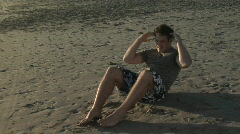 A man does sit-ups on a sandy beach. Stock Footage