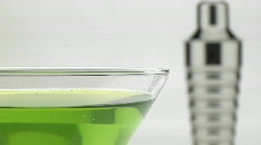 A silver martini shaker sits behind a glass with green Stock Footage