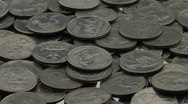 Stock Video Footage of Quarters lay in a pile on a white surface.