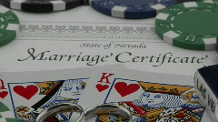 A marriage certificate sits nestled under playing cards and Stock Footage