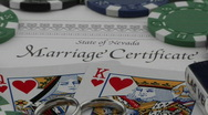 Stock Video Footage of A marriage certificate sits nestled under playing cards and