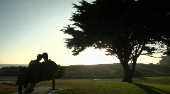 A couple snuggles on a park bench. Stock Footage