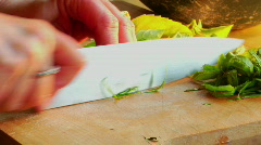 A woman chef preps a salad by chopping basil on a wooden Stock Footage
