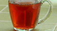 Sugar poured into a clear glass cup of tea and stirred with a spoon. Stock Footage