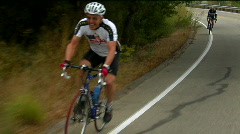 Bicyclists pedal around a mountain curve. Stock Footage