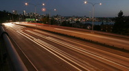 Stock Video Footage of Traffic drives along a Seattle freeway at night.