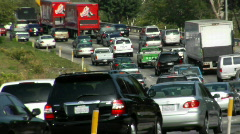 Heavy traffic moves bumper-to-bumper along a four-lane highway. - stock footage