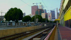 The L.A. Metro train emerges with the city skyline background. Stock Footage