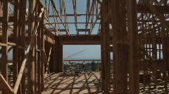 A contractor carries a piece of wood in an unfinished home. Stock Footage