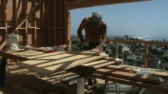 A contractor hammers on a piece of wood and carries it away. Stock Footage