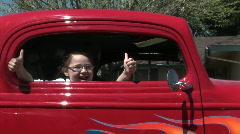 Nuori tyttö antaa kaksi peukkua ulos auton ikkunasta. Arkistovideo
