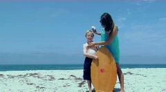 A woman rubs sunscreen on a boy at the beach. Stock Footage