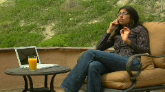 A woman speaks into a cell phone while sitting on a patio. Stock Footage