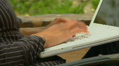 A woman works on a laptop computer in an outdoor setting. Stock Footage