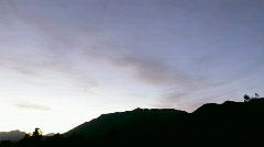 Clouds move over a silhouetted mountain during golden hour. Stock Footage