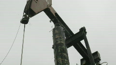An oil pump-jack rises and falls as clouds pass across a blue sky in time lapse. Stock Footage