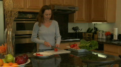 A woman slices tomatoes on a cutting board in her kitchen. Stock Footage