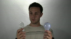 A man holds a compact-fluorescent light bulb in one hand and a standard light Stock Footage