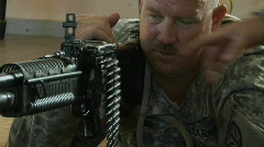 A man prepares to fire an automatic weapon. Stock Footage