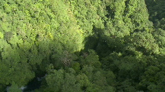 Aerial over a Mountain Range covered in Rain Forest revealing river & Waterfall - stock footage