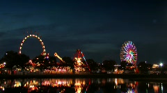 Ferris wheel and carnival rides at dusk - stock footage
