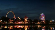 Ferris wheel and carnival rides at dusk Stock Footage