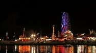 Carnival rides and amusements reflecting on lake Stock Footage