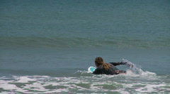 Surfer paddels out towards the waves Stock Footage