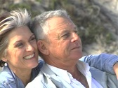 Stock Video Footage of Mature couple on beach pan NTSC