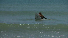 Surfer waiting for a surf-able wave and paddles towards the camera as a little  - stock footage