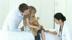 Asian doctor checking little girl's reflexes - stock footage