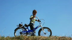 Boy with bicycle drinks water from bottle and goes. time lapse Stock Footage